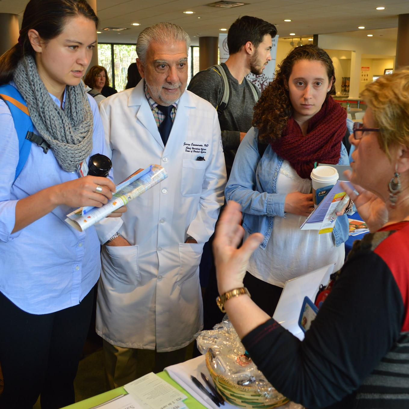 TouroCOM-Middletown D.O. student Andrea Attenasio, far left, speaks to a representative at the JMHCA Fair in October 2015.