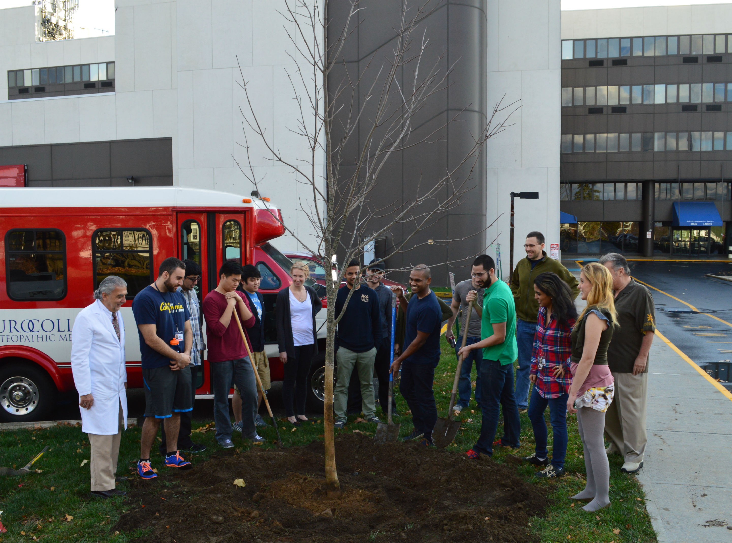 Students from the class of 2018, and faculty, gather around the newly planted Crimson King maple tree during its dedication ceremony.