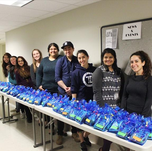 First-year Osteopathic Medical Students stand with their homemade care packages, ready to hand out to the second-year students.