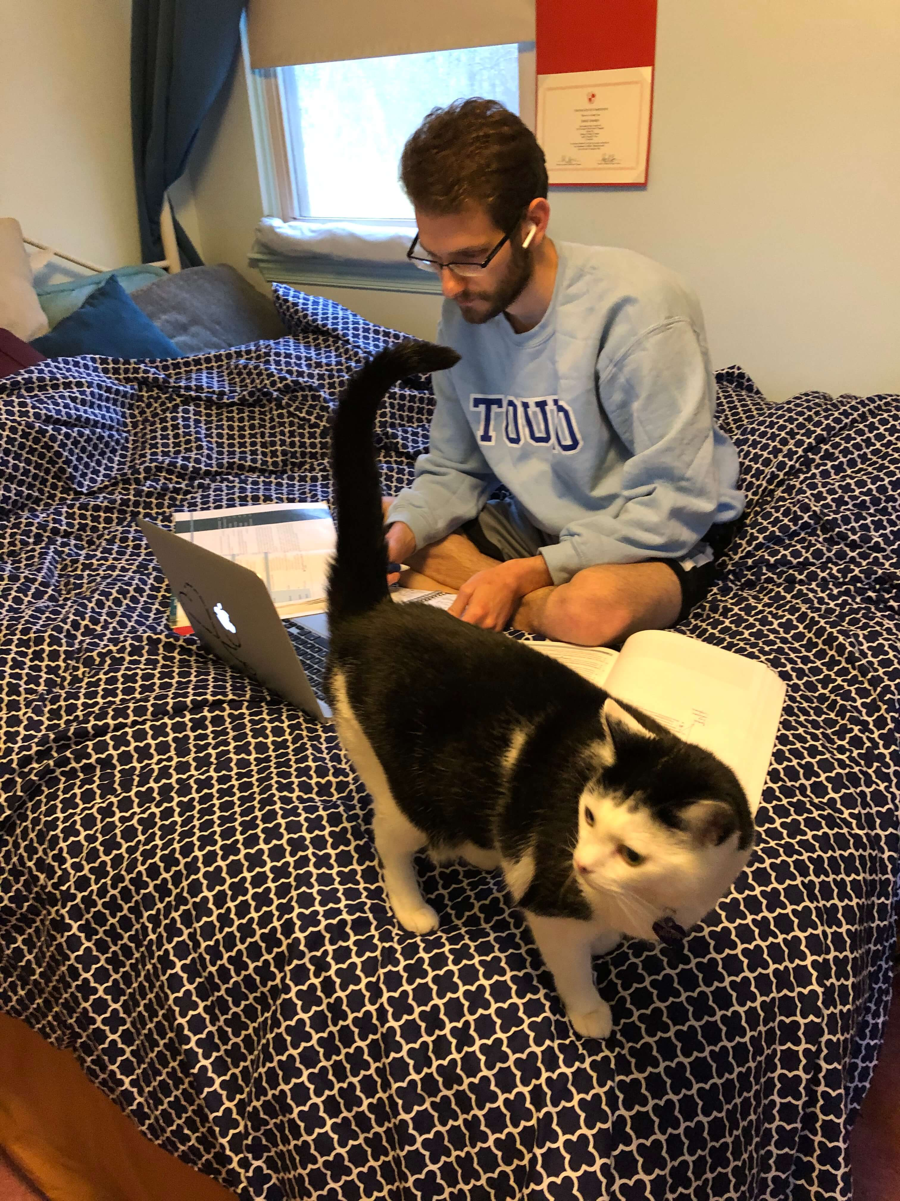 "Adam Halpern, OMS II, studying with Hilly the cat in Pennsylvania while school is closed for ""Stay-at-Home"" in New York"