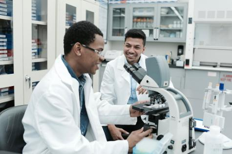 two males, high school student Jordan McDonald, and a medical student Kowshik Sen, sitting on stools in a lab smiling and talking while the older one teaches the younger one how to use a microscope that is sitting on a white counter in the lab