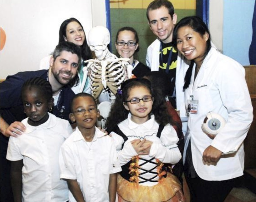 Eric French (far left), a first-year medical student at Touro College of Osteopathic Medicine in Harlem, taught 8-year-old Tatjana Quinones (bottom row, far right) about healthy bones at a Halloween event at her elementary school, P.S. 197, also in Harlem.